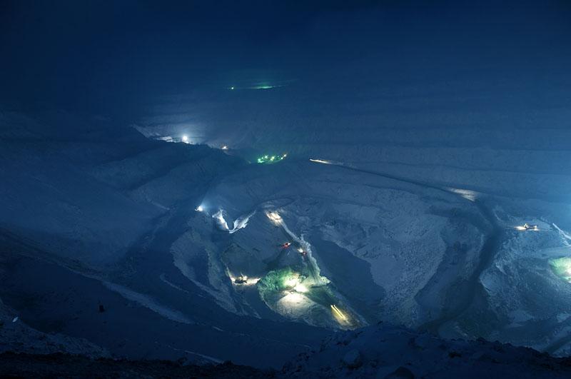 Norilsk se situe sur le plateau de Sibérie occidentale et au pied des montagnes de Putoran, culminant à 1700 mètres d'altitude. Norilsk possède les plus importants gisements de nickel, de cuivre et de palladium dans le monde. Ce dépôt a été formé il y a environ 250 millions d'années lors de la formation de la Sibérie. Aujourd'hui, l'entreprise de Norisk « Norilsk Nickel » est devenu le premier producteur mondial de palladium, minerais représentant 40% de la production du combinat. Avec 36% de la production mondiale, Norilsk se retrouve aussi au premier plan de la production de platine. Ces production assure près de 2% du PIB russe : janvier 2001, le palladium se négociait à plus de 1 000 dollars de l'once et à 480 dollars l'once en avril 2008. Le Nickel s'adjuge lui à 25 000 dollar la tonne. En 2007, Norilsk Nickel, qui contribue à 90% du budget de la ville, a produit : - plus de 300 000 tonnes de nickel (96% de la production russe et 30% de production mondiale), - 419 000 tonnes de cuivre (55% de la production russe) - 93 tonnes de palladium (35% de la production mondiale) - 22 tonnes de platine (36% de la production mondiale) Selon les dernières estimations, les réserves du sous-sol de Norilsk permettraient de soutenir une production de ce niveau pour les 50 années à venir. Sur la photo - la mine ouverte « Medvejii Ruchei ». Malgré le climat rude, la température qui descend jusqu'au -50° et les tempêtes de neige, ces mines ouvertes fonctionnent 24 heures/24 toute au long de l'année.